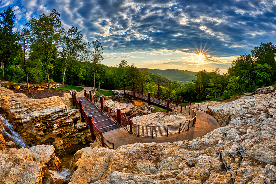 Cave trail carved out of the rock in the Ozark Mountains with vivid sky and sunset