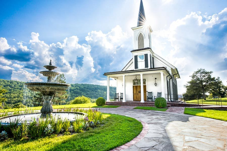 Garden Chapel at Big Cedar exterior view of water fountain and sun peaking around the steeple overlooking the valley