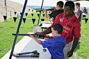 Young boy being taught how to shoot an air riffle at the Air Riffle Bullseye event at Big Cedar