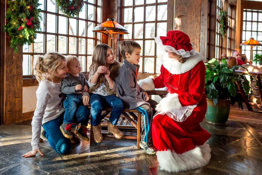 Mrs. Clause sitting next to four children telling a story in the lobby of the Registration building