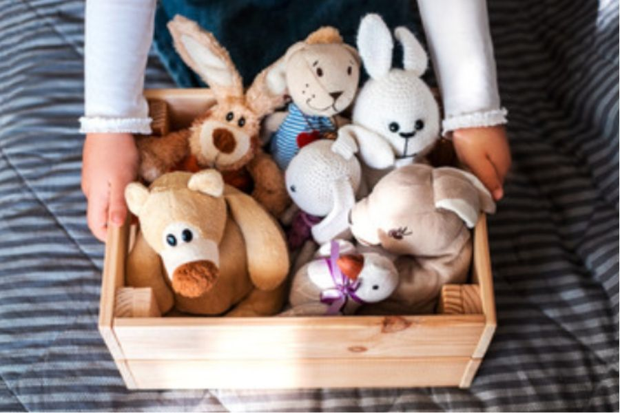 Child holding a box of stuffed animals