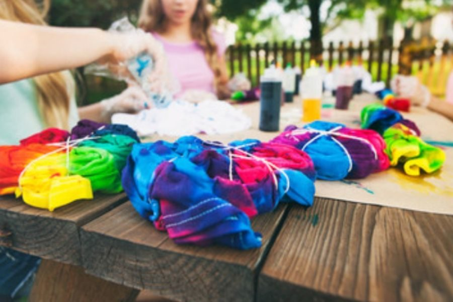 Children tie dying t-shirts on rustic wooden table