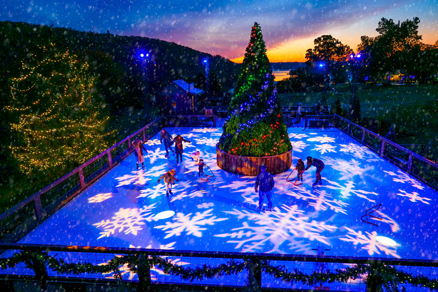 Big Cedar's Ice-Rink at night with projected snowflakes on the ice and large Christmas tree in the center.