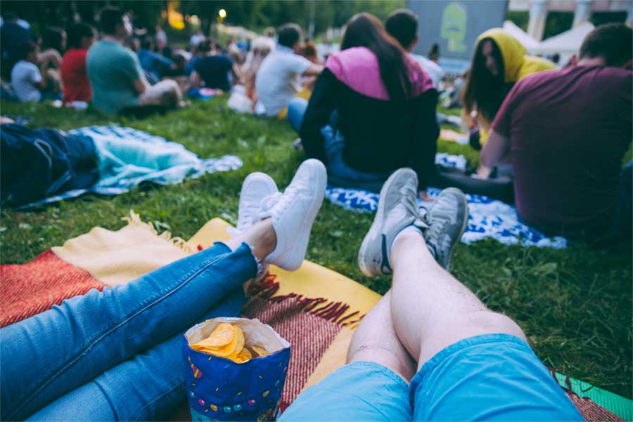 People enjoying a movie on the lawn with snacks