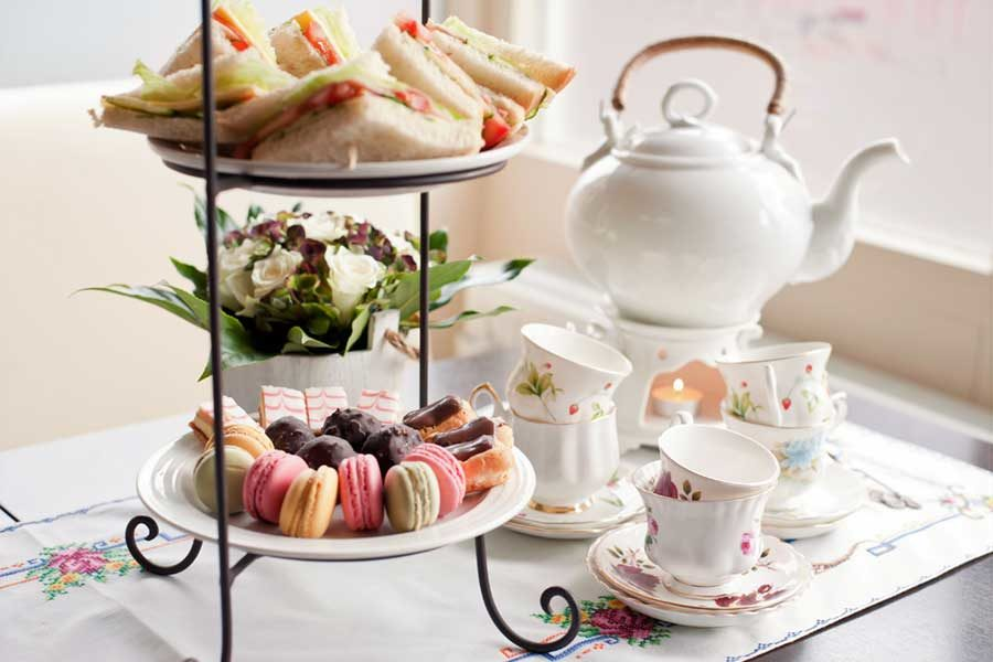 Tea Party Display with a tea pot, tea cups, and finger foods.