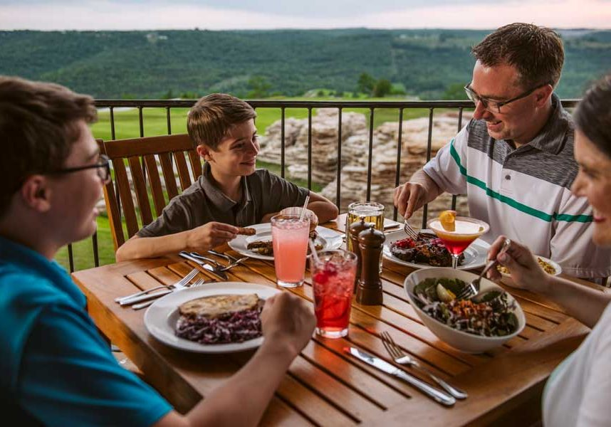 Family of four enjoying a delicious meal overlooking the golf course at Mountain Top Grill