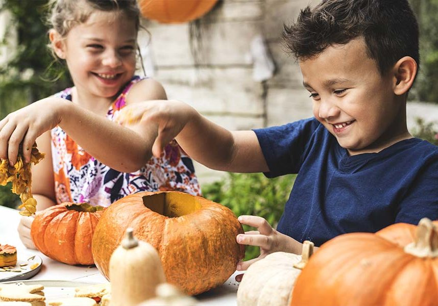 Two children pulling the filling out of pumpkins