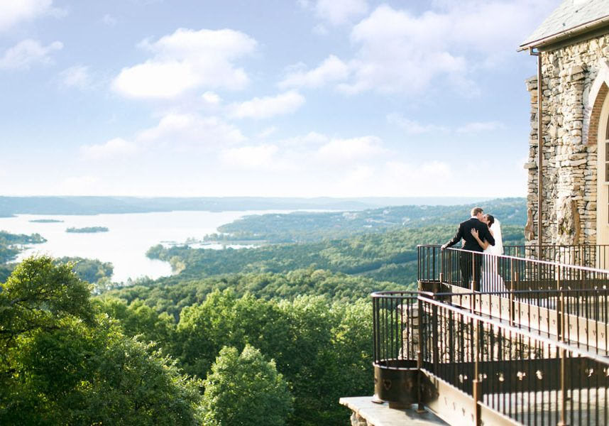 Bride and groom kissing on the balcony of a Big Cedar Top of the Rock chapel with Table Rock Lake in the distance.
