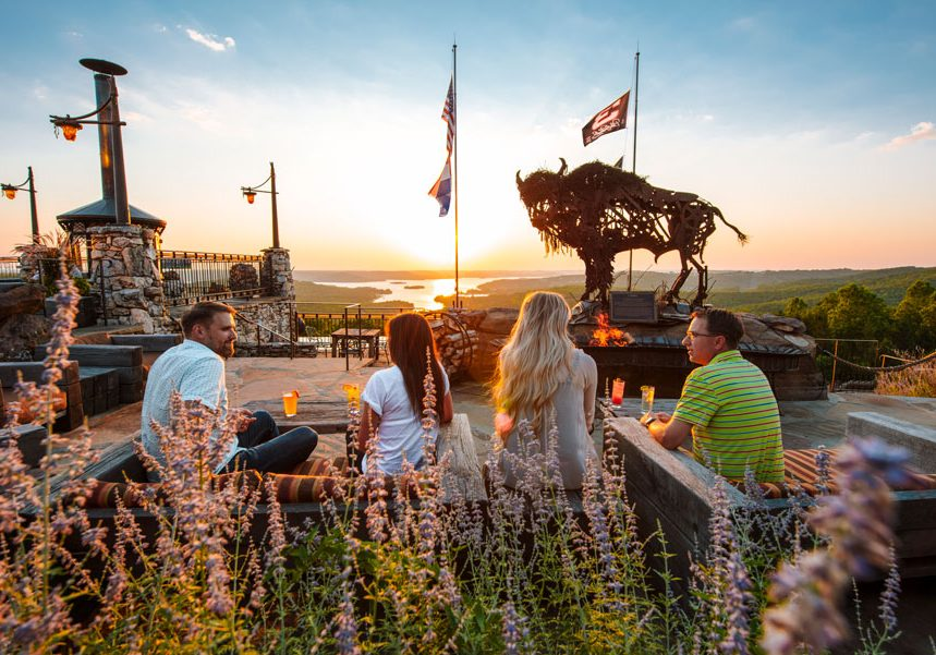 Couples on the patio at Buffalo Bar enjoying outdoor casual dining with view of the valleys and Table Rock Lake at Top of the Rock at Big Cedar