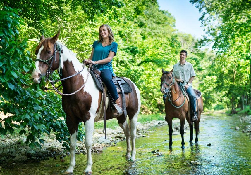 Young couple on horseback riding trails at Dogwood Canyon Nature Park at Big Cedar